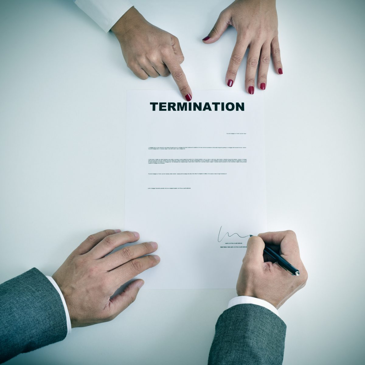 man signing wrongful termination contract who is going to seek the legal help of a trusted wrongful termination attorneys Chicago