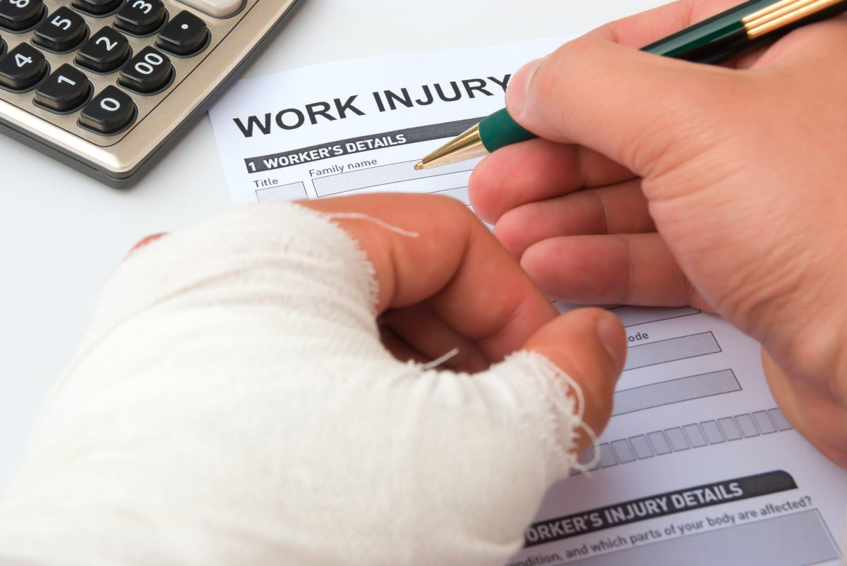 a person filing a work injury claim form with the help of an experienced Chicago work injury lawyer