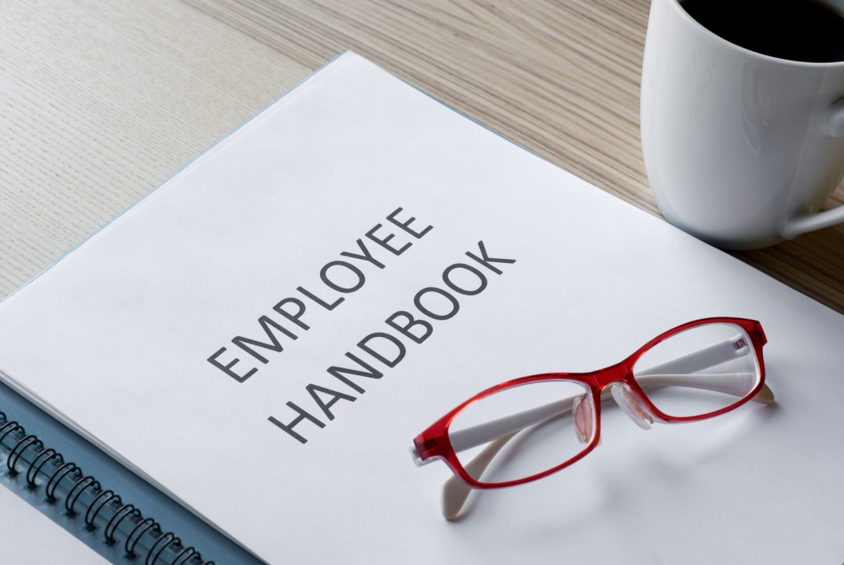 employee handbook with red glasses of a trusted chicago harassment lawyer