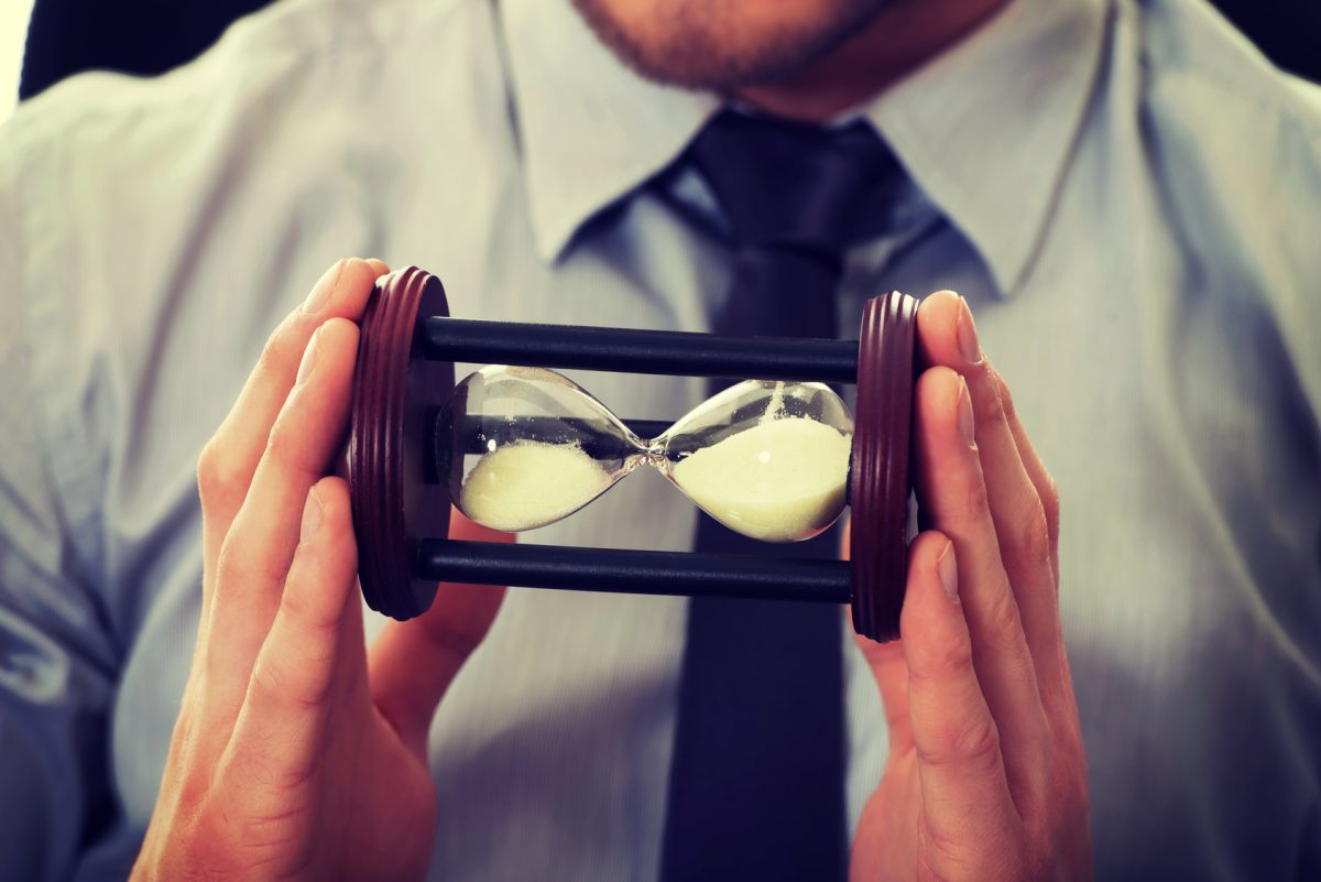 businessman holding hourglass representing the time that it takes to call a chicago compassionate harassment lawyer