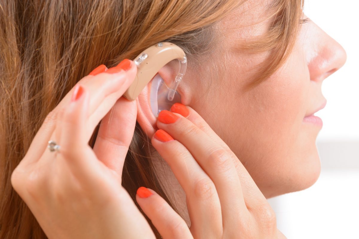 person putting on a hearing aid after discussing a case with a chicago top discrimination lawyer