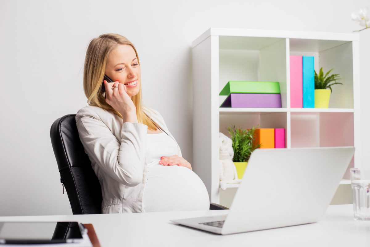 pregnant woman working at the office, that is starting to see some discrimination. Contact a skilled pregnancy discrimination lawyer in Chicago.