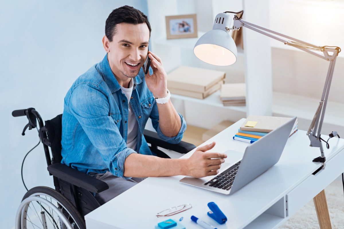 Man sitting in his wheelchair at desk at his job, if you are being discriminated at work contact our ADA Employment Lawyer River North.