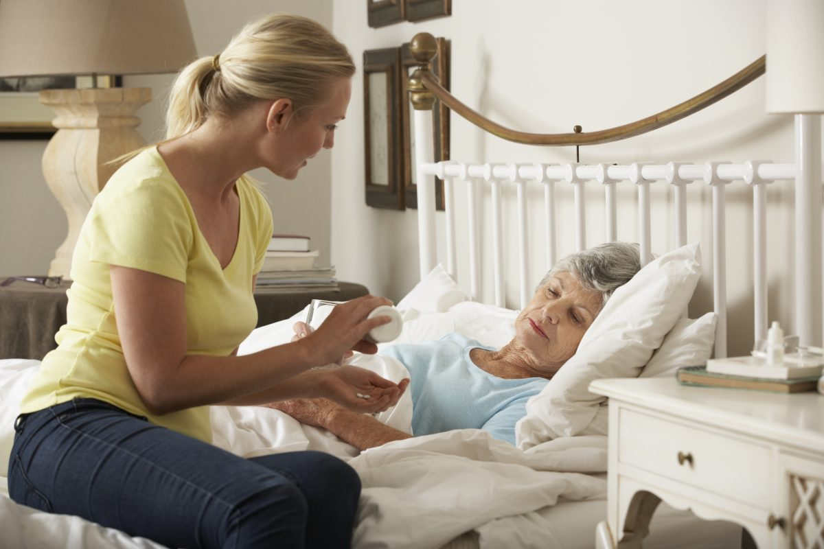 An adult woman caring for her senior mother in bed, if your job isn't allowing FMLA rights speak to our FMLA Discrimination Attorney Chicago.