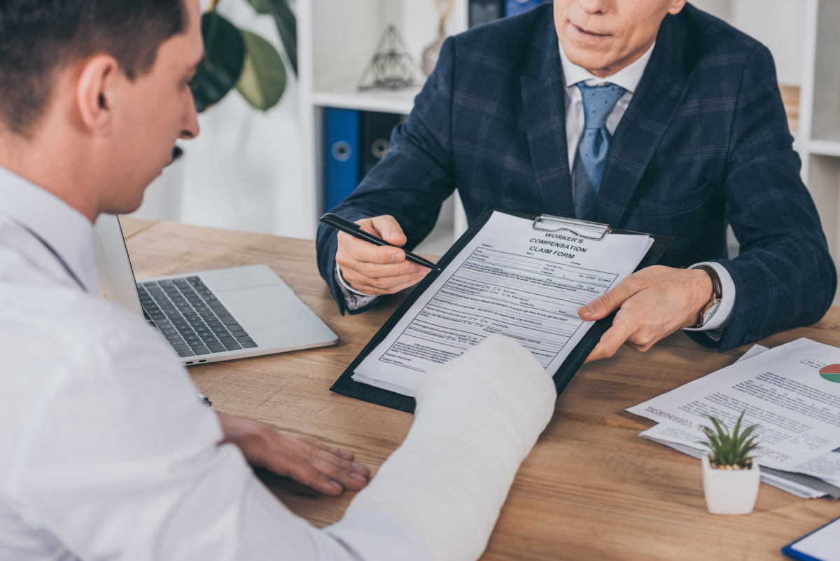 A lawyer to talking to a man who is wearing an arm cast, representing how one can benefit from contacting a Chicago worker's compensation lawyer.