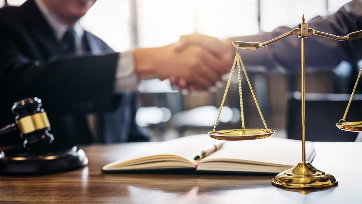 A lawyer shaking hands with a client in his office next to a golden scale, representing how one can benefit from calling a Chicago discrimination attorney.