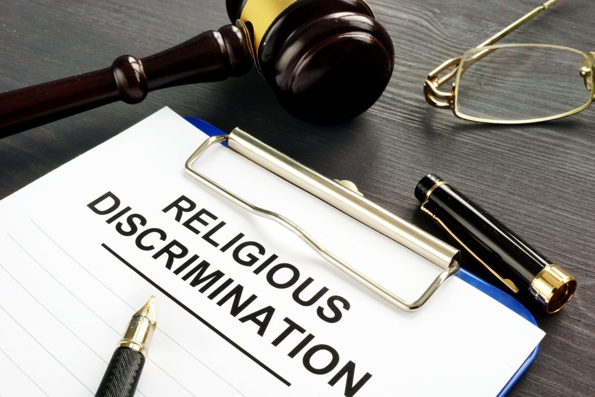 A clipboard, pen and gavel on the desk of a religious discrimination lawyer in Chicago.