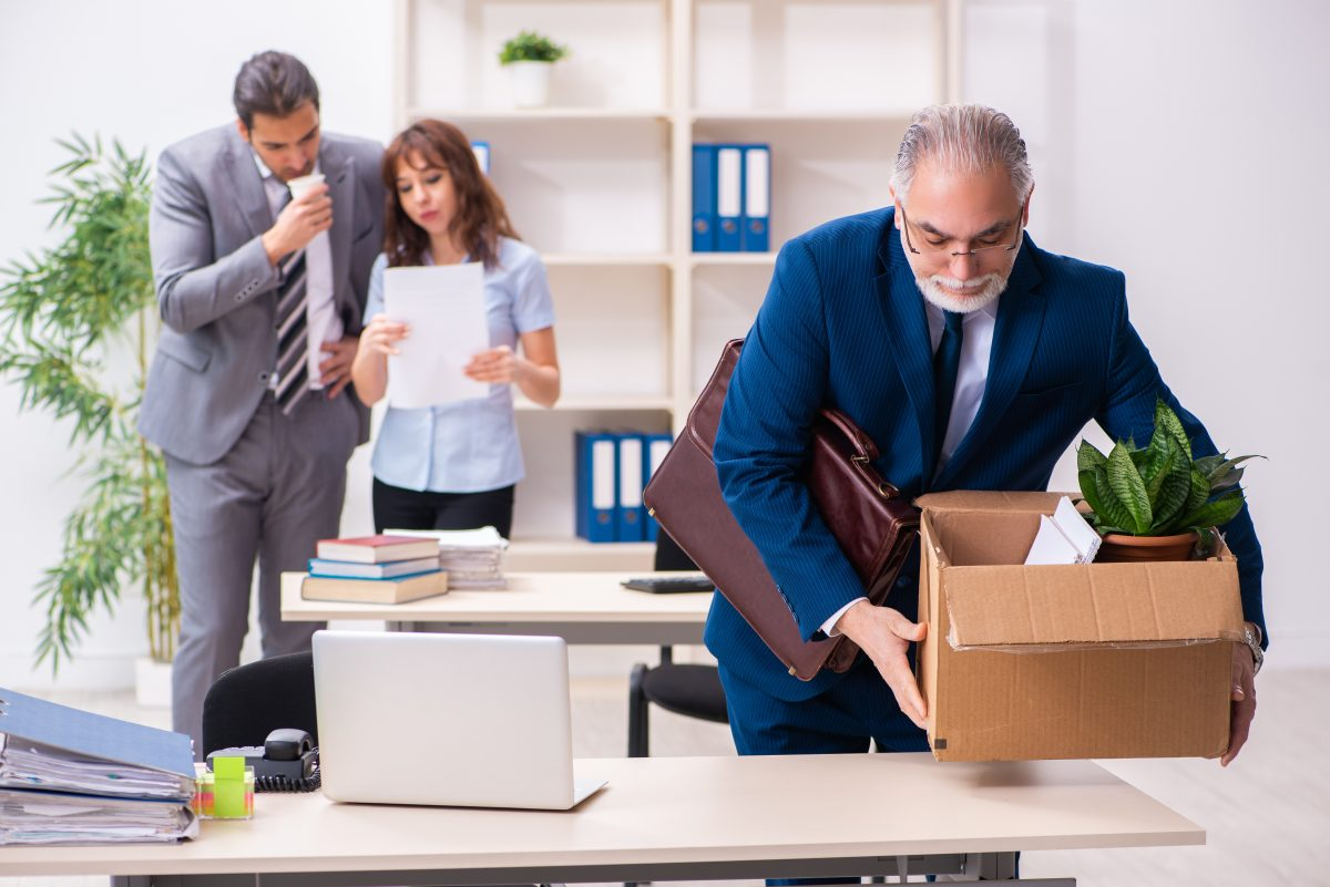 Two employees looking at document while an employee packs up his belongings before calling a Chicago employment discrimination lawyer.