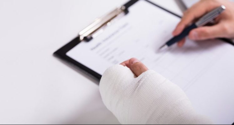 A person with a broken arm filling out workers compensation documents after meeting with our Chicago employment law attorneys.