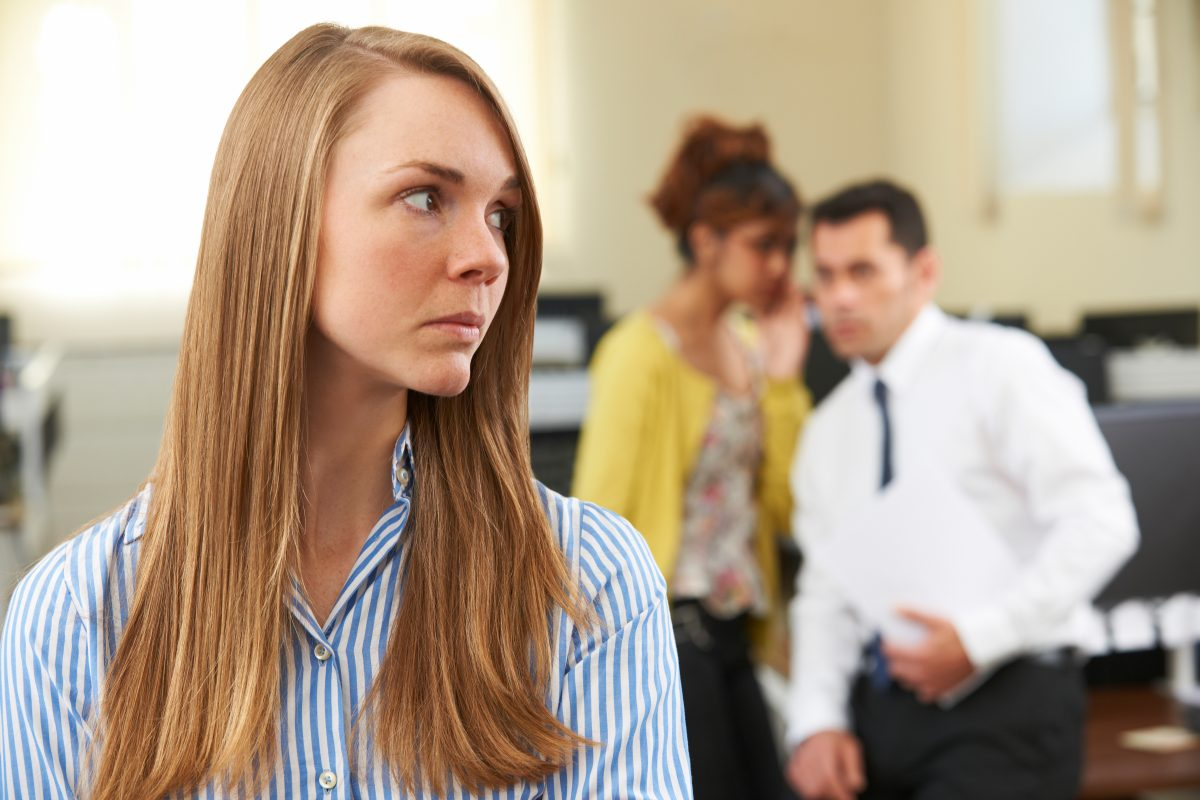 Two employees gossiping about another employee in an office representing how a Chicago employment lawyer can assist you with your harassment case.