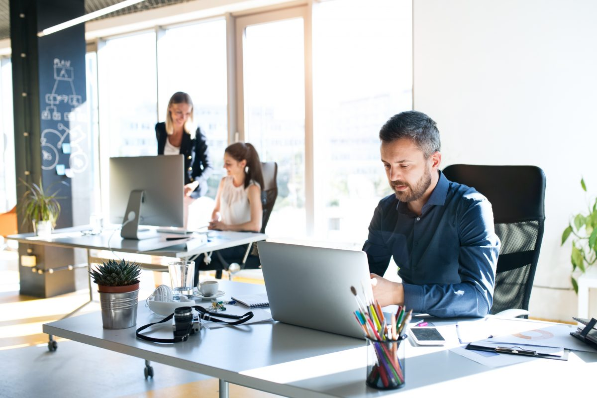 Office employees sitting at their desks representing how a Chicago employment lawyer can help you determine if you're in a hostile work environment.