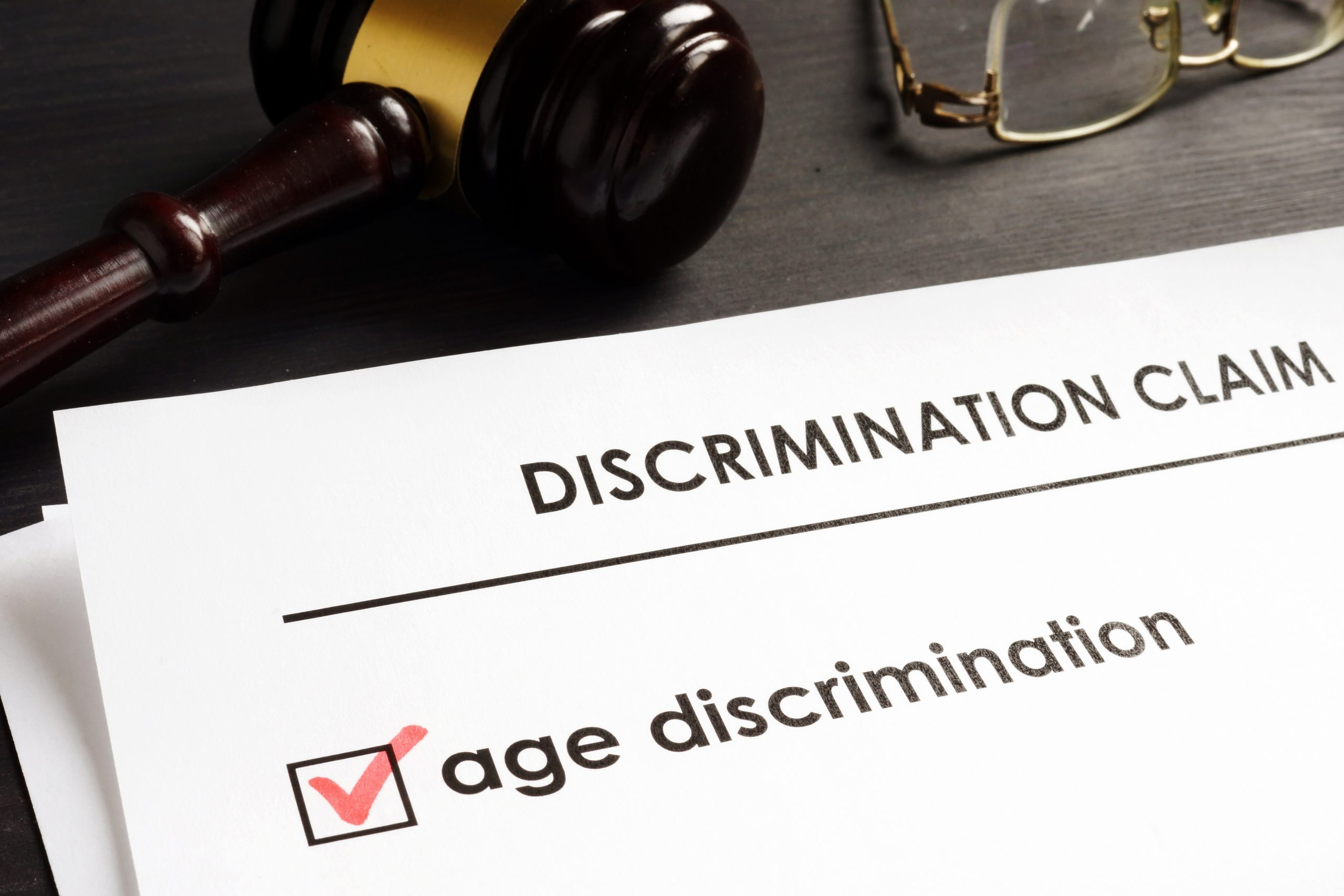An age discrimination claim, glasses and a gavel on the desk of a Chicago age discrimination attorney.