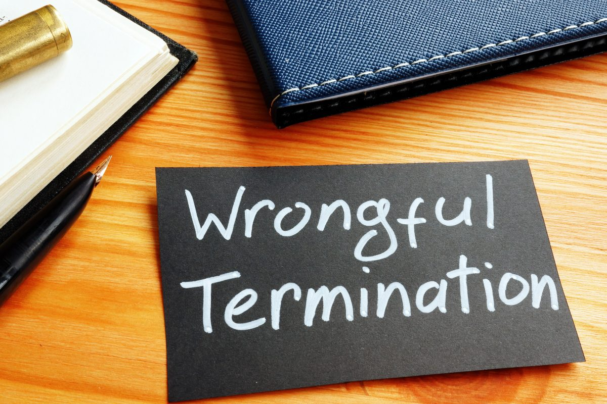 A notebook and a black piece of paper with words 'wrongful termination' written on it on the desk of a Chicago wrongful termination lawyer.