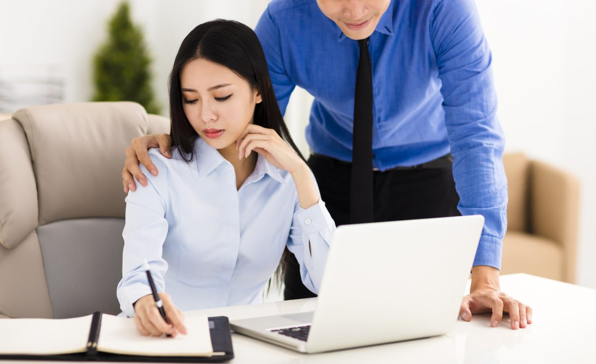 Businessman harassing colleague in the office, meet with a Chicago workplace harassment attorney for help.