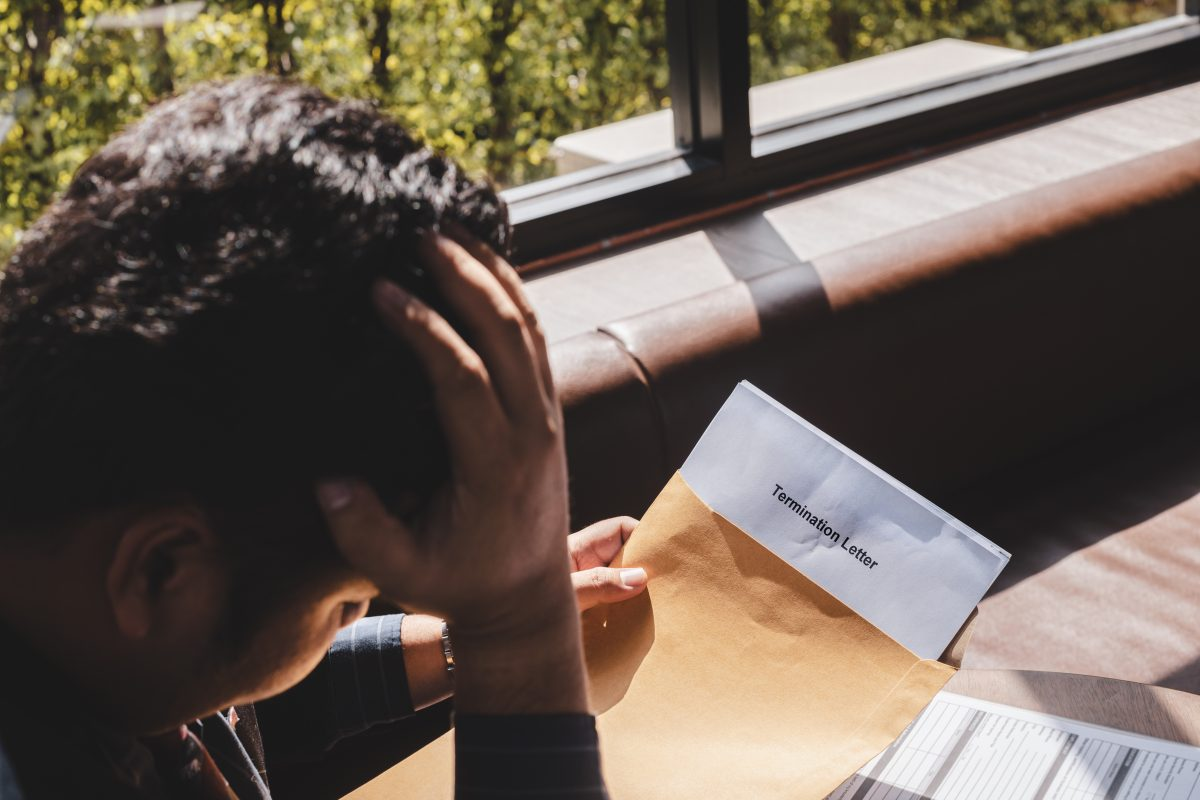 A businessman looks down at his termination letter, meet with a Chicago wrongful termination attorney for help.