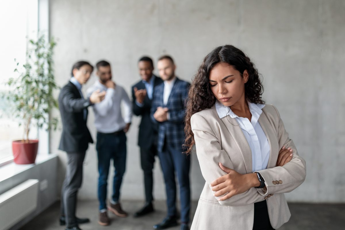 Woman standing alone looking upset, group of male employees stand behind laughing at her, deciding to call her Illinois Employment Attorney for help.